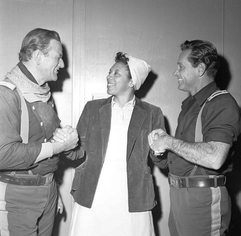 """. Actors John Waynes, left, and William Holden, right, congratulates tennis star Althea Gibson in Los Angeles, Dec. 24, 1958, Gibson is making her movie debut with  upon her selection for the second straight year as female athlete of the year in the annual Associated Press poll. Gibson is making her movie debut with Wayne and Holden in \""""Horse Soldiers,\"""" under production in Hollywood. (AP Photo/Harold Filan)"""