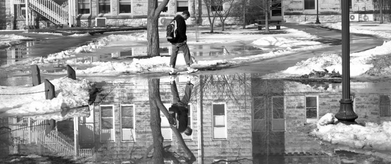 """Jay Grabiec/The Daily Eastern News<br /> An Eastern student pulls up his pant legs while attempting to cross a large puddle in front of Old Main on Tuesday afternoon.  Although workers from physical plant were trying to clear the water with tractors in between classes the water would not receed.  Some students called the puddle """"the swamp"""" and """"Mini Lake Charleston""""."""