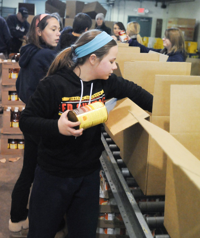 . Pottstown High School and Pope John Paul II students a to pack boxes of food at the Mercury for Operation Holiday delivery. ERin Cannon packs food.Photo by John Strickler/The Mercury