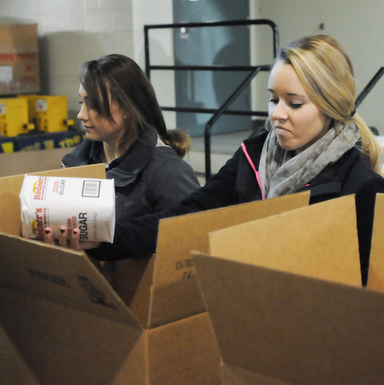 . Pottstown High School and Pope John Paul II students a to pack boxes of food at the Mercury for Operation Holiday delivery. Tori Gery and Megan Remick pack food. Photo by John Strickler/The Mercury