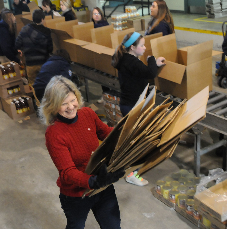 . Mercury editor Nancy March pitches in during Operation Holiday food packing. Pottstown High School and Pope John Paul II students  packed boxes of food at the Mercury for Operation Holiday delivery. Photo by John Strickler/The Mercury