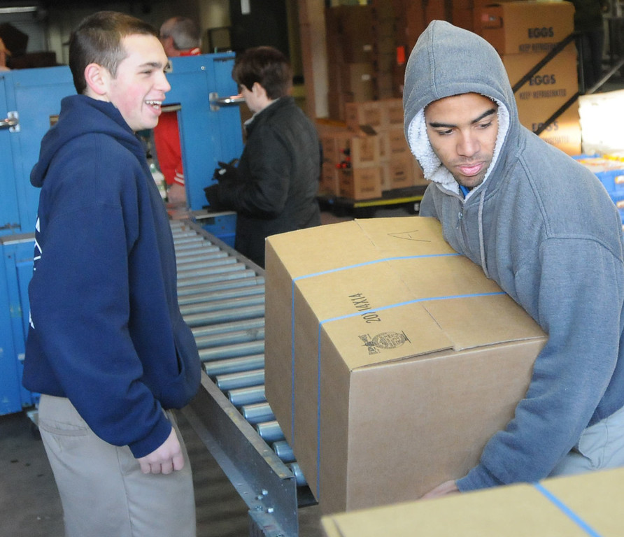 . Pottstown High School and Pope John Paul II students a to pack boxes of food at the Mercury for Operation Holiday delivery. Nate Fuerman and Soloman Bailey load boxes of food. Photo by John Strickler/The Mercury