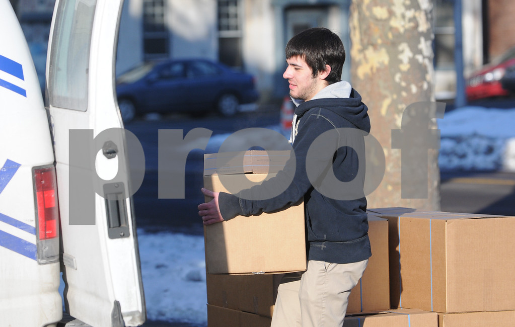 . Pottstown High School and Pope John Paul II students  pack boxes of food at the Mercury for Operation Holiday delivery. Jeff Vontor loads boxes onto Mercury vans.Photo by John Strickler/The Mercury