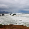Angry surf surrounds the Cannon Beach areas and Haystack Rock in the distance