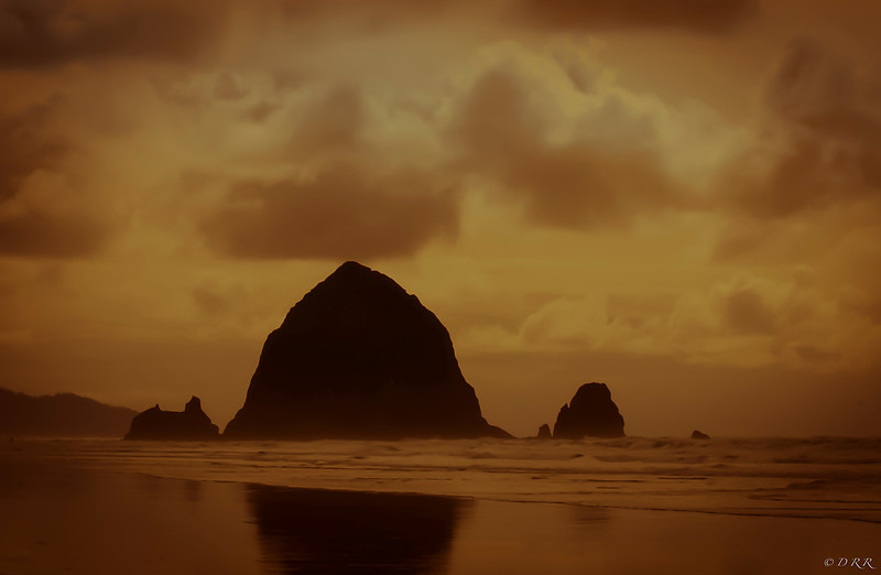 "This is my version of Haystack Rock at Canon Beach Oregon. This area has a love of photographers from all around the world.<br /> ""I wanted to express my work in a silhouette reflection from the water and waited until late evening almost a tobacco reflection with the sun""."