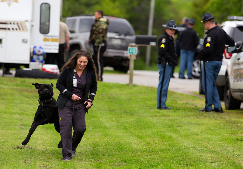 ORRINGTON, Maine -- 06/06/2017 - A woman picks her dog up for doggie day care while Maine State Police, Penobscot County Sheriff, and Brewer police work to talk to a man who reportedly barricaded himself inside his home near the intersection of Johnson Mill Road and Center Drive in Orrington Tuesday. Ashley L. Conti | BDN