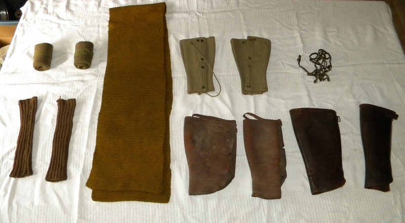 Uniform accessories: Top, L-R: puttees (cloth wrappings for the lower legs), a very thick neck scarf, canvas leggings, string with pins (perhaps for the puttees??).<br /> Bottom, L-R: wrist warmers, leather leggings (very worn), and a second set of leather leggings (for dress??).
