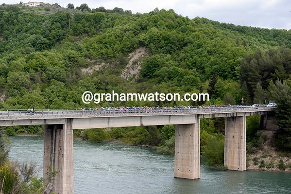The peloton crosses a bridge over a massive reservoir somewhere in Basilicata...