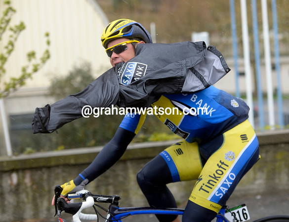 Nicholas Roche is struggling to get his rain-jacket on, again, as the wind and rain start to bite...