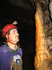 Photographer cred to Adam Byrd.  Scott looks at a gorgeous orange stalagmite in the decorated passage.