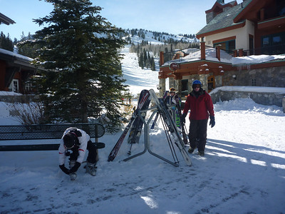 Holly latching down her ski boots,  Ronzo in the red jacket