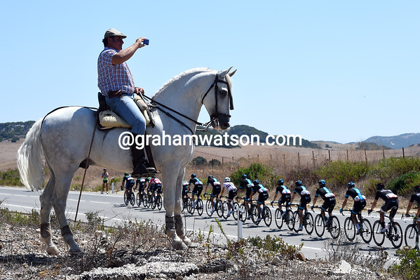 A horseman and his beautiful mount look down on the peloton as it races towards the hills...
