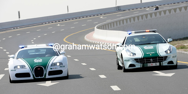 A Bugatti police car driven by a man, and a Ferrari police car driven by a woman, form the escort for the Dubai Tour today...