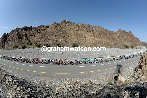 The mountains of northern Oman dwarf the peloton as it chases the escape...