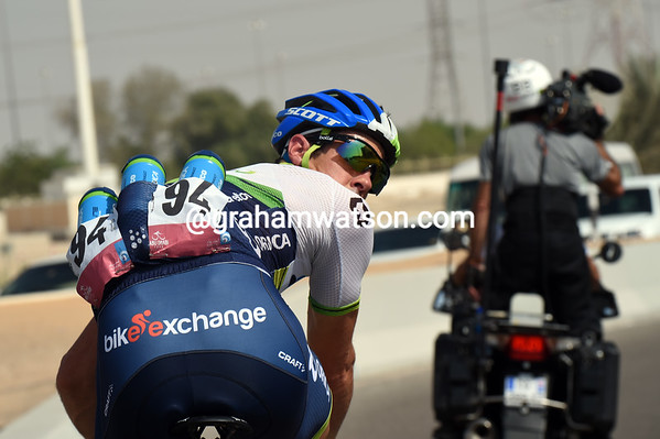 Matthew Hayman is looking back for his team car and to dispose of empty water bottles...