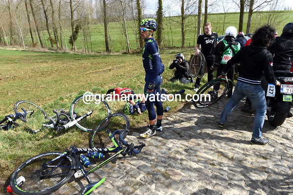 Injured cyclists lie everywhere, including three from Movistar...