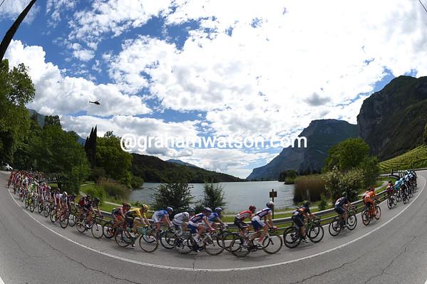 The peloton circles a pretty lake somewhere in Trentino...
