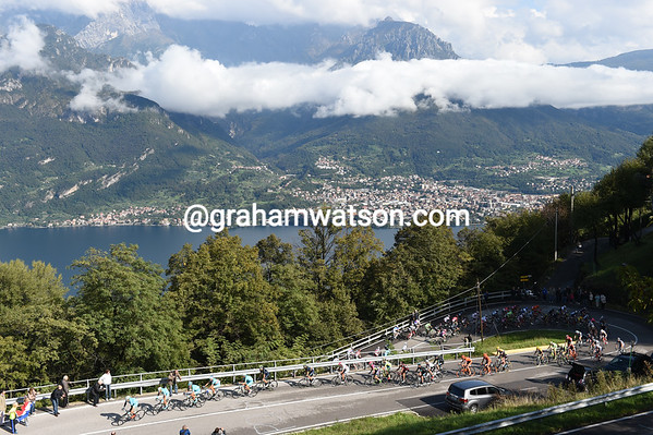 Astana leads the peloton up the Ghisallo with the sun and cloud over Lake Como fighting for attention...