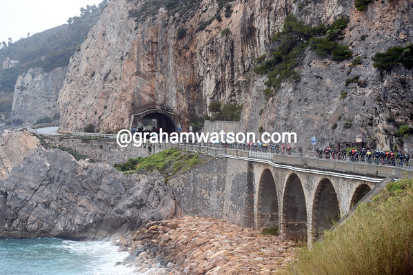 The peloton is in single file along the exposed coastline...