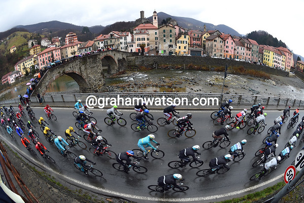 The peloton speeds past the village of Campo Ligure on the ascent to the Turchino Pass...
