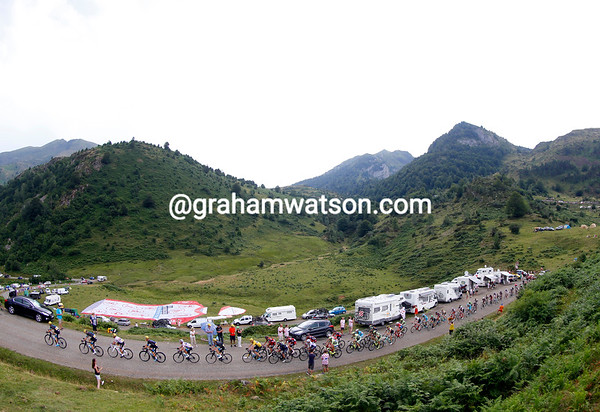 The Sky-led peloton crosses the Port de Lers summit as the skies darken above them...