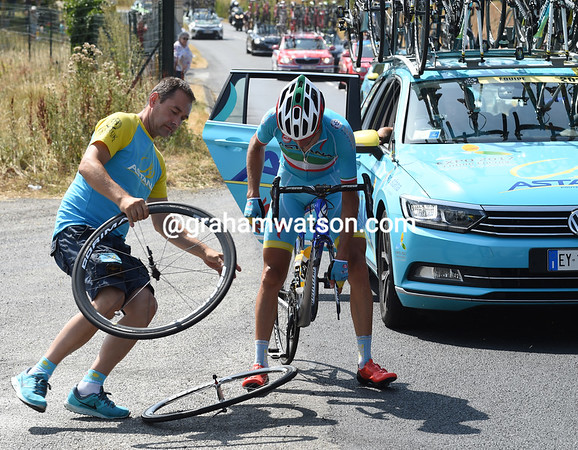 Nibali is making his second wheel-change in a few minutes, but he's burnt his hand taking the front wheel out after a long descent..!