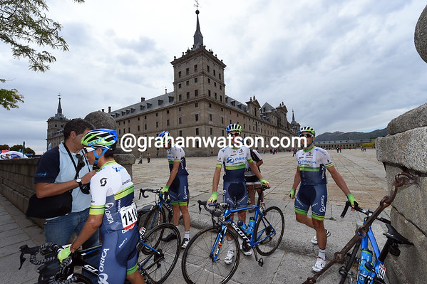 Some Orica-Green Edge cyclists arrive at the start after a look at the Monestario de El Escorial...