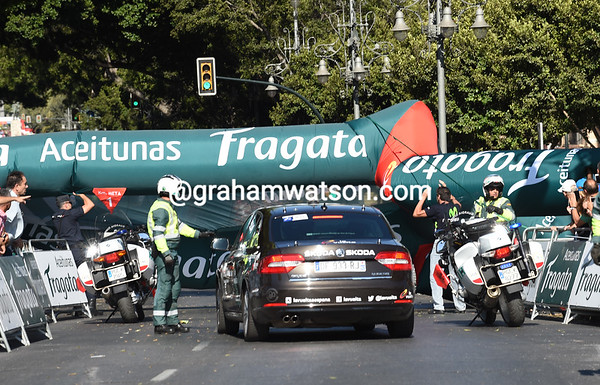 The last-kilometre plastic arch has blown over in the centre of Malaga, but police clear it away just in time..!