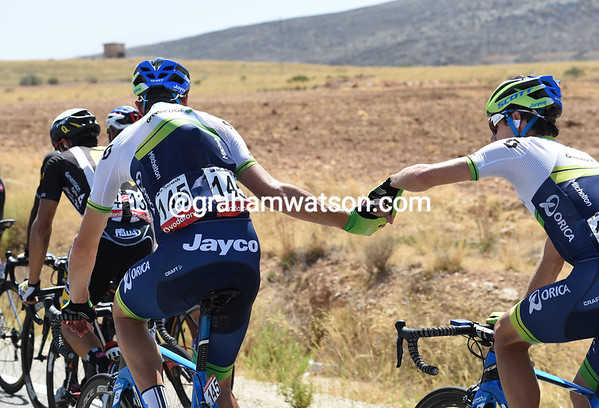Matthew Hayman works at the back, handing ice-cubes to teamates like Daryl Impey...