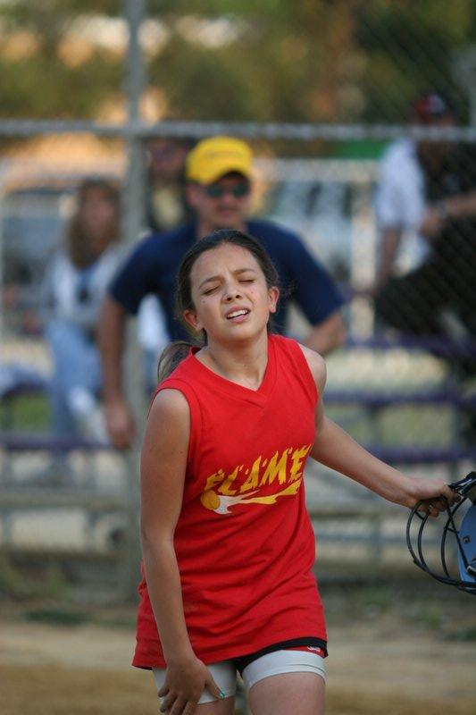 After doing a 360 summersalt over the catcher at home plate, this young fastpitch player makes her way to the dugout.