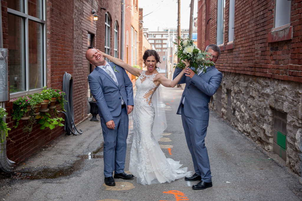 Bride takes a playful photo with the groomsmen