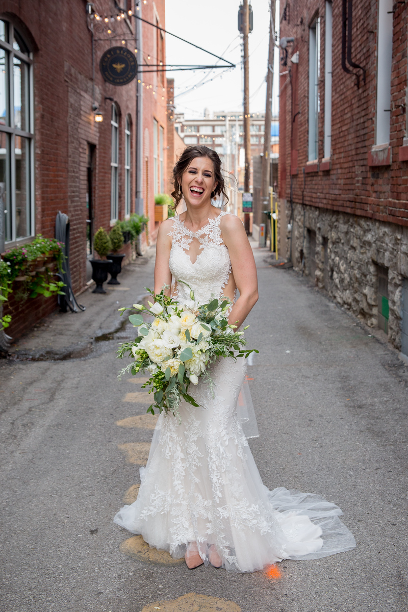 Bride takes a playful photo in the alley
