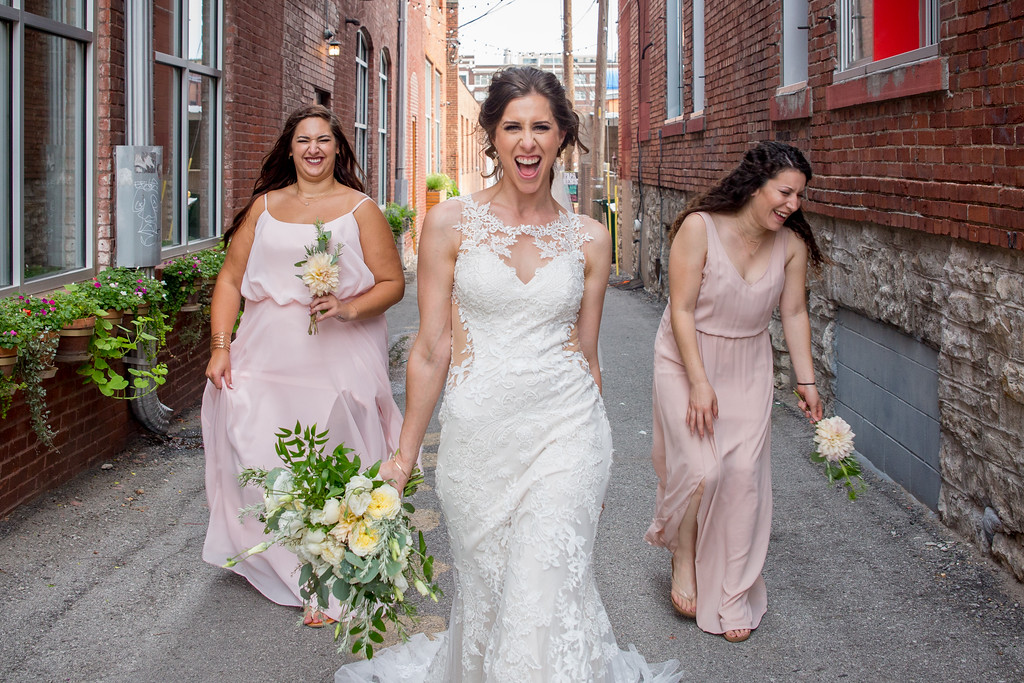 Bride takes a playful photo with her bridesmaids