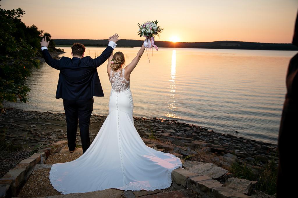 Celebratory lakeside shot of bride and groom