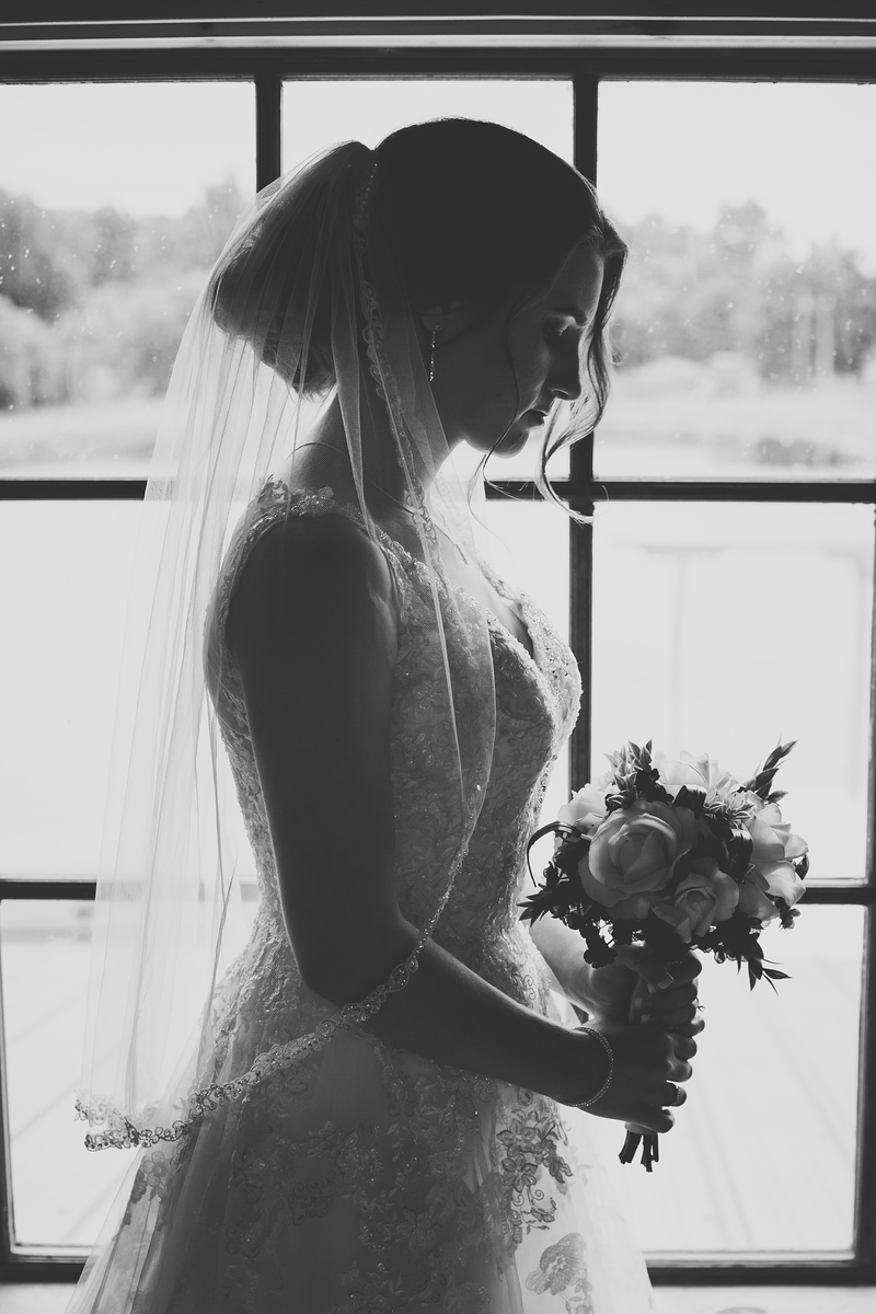 black and white photo of bride near large window