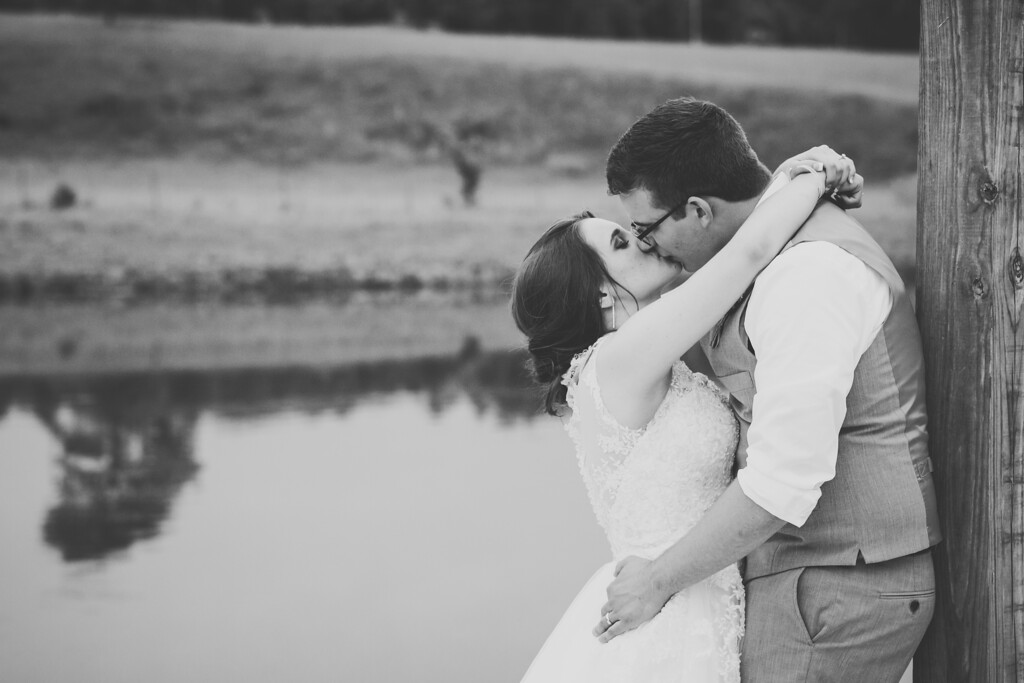 Bride and groom share a kiss by the water