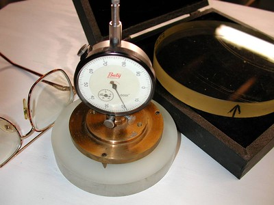 """This is an original spherometer made by the world famous telescope and instrument maker """"Horace Dall"""" sitting on a 4.25 inch Pyrex telescope mirror blank.  I obtained this device directly from a former telescope maker in England and have all documentation on this including letters from Mr.Dall himself!  Horace Dall is the co-inventor of the Dall-Kirkham Cassegrain Telescope. Also pictured is a 6 inch optical flat used for referencing the dial indicator on the spherometer.  Al Paslow telescope collection."""