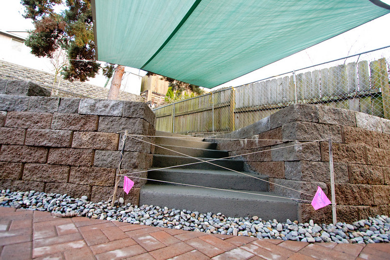 Patio in, french drain finished, and stairs poured.  The temporary tarp is to protect the stairs from rain as the concrete sets.