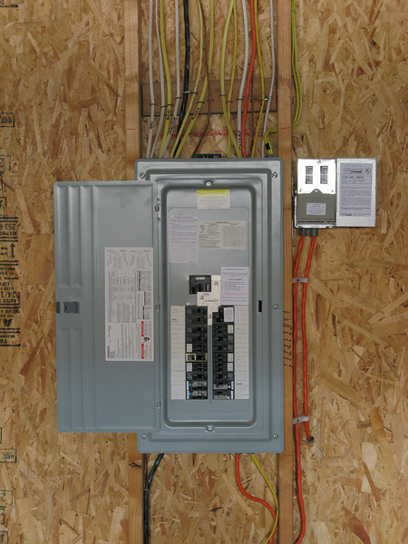 Modified panel with generator breaker, mechanical interlock, and new circuit for driveway sump pump.  Generator power meter to the right of electrical panel.