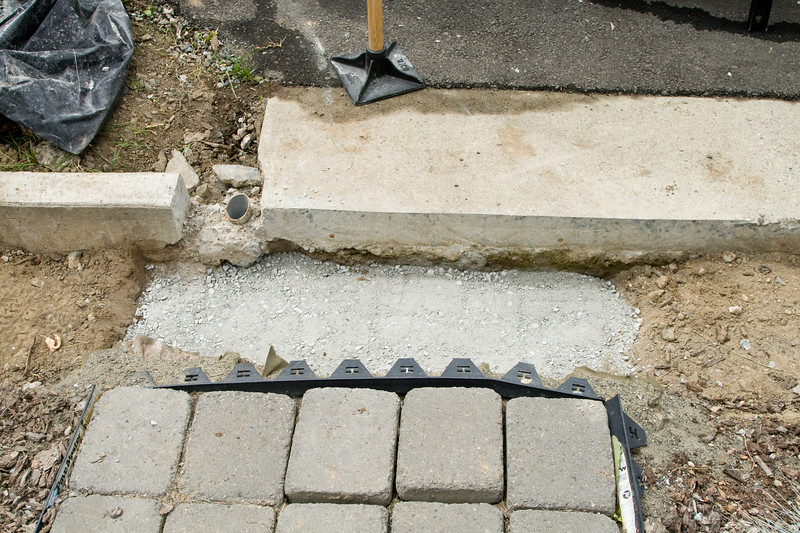 After attempting to break the concrete away with the pick ax, we eventually decided to fill with sand and gravel until it was covered, resulting in a higher first step than planned.