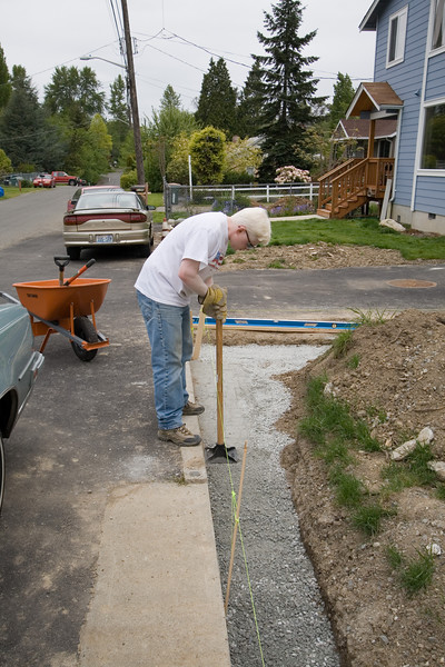 Ben tamps in the first 2-inch layer of sand and gravel foundation