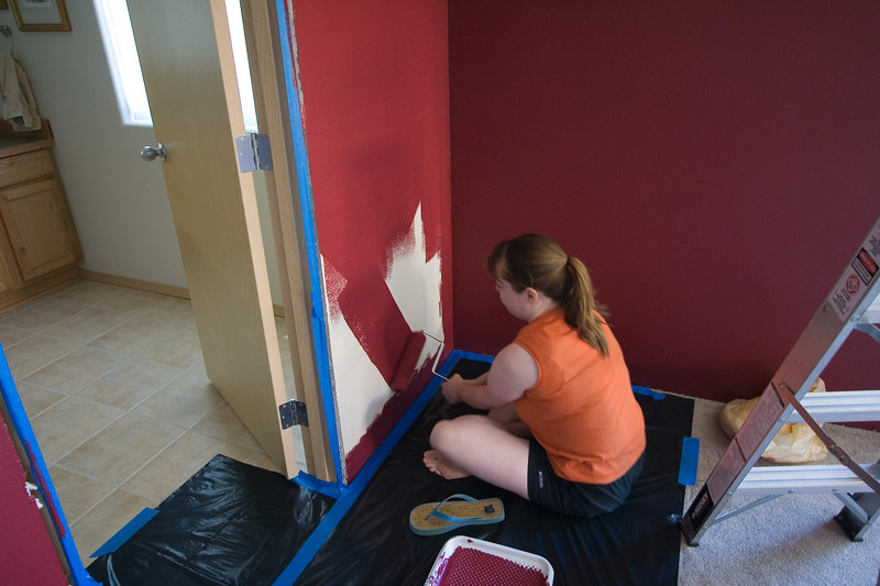 Sarah rolls on the last bit of red paint, completing coverage on the last wall in the bedroom.  Still another coat to go though...