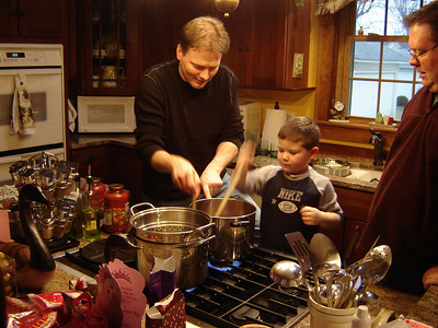 Owen helps out with cooking under the guidance of Tim and Bob.
