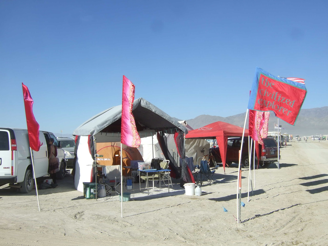 Our camp from the street. Van, shade, tent, and flags. The red shade is our neighbor's.