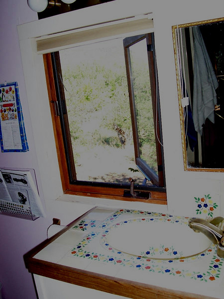 """The """"cozy"""" (tiny) upstairs bath has nice tile and a great view into the side yard and out toward Black Mesa."""