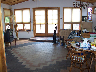 The sunroom with its artistic brick floor and stained-glass windows. Boxes were piled here while we worked on the rest of the house.