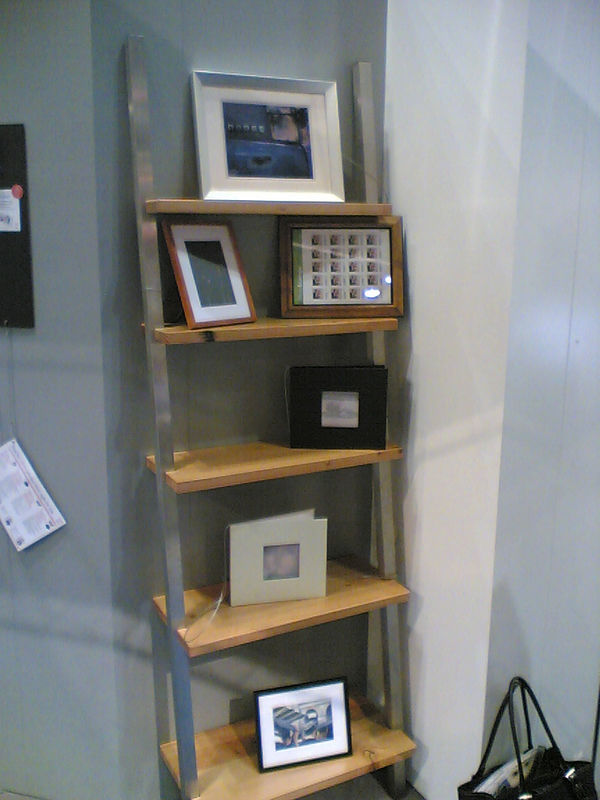 The shelf had some framed prints, stamps, and some books.