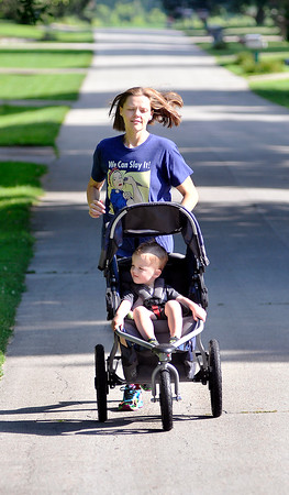 John P. Cleary | The Herald Bulletin<br /> Lindsey Dollar, with 2 year old son Galen in the stroller, go around the neighborhood for their morning walk, or jog, everyday.