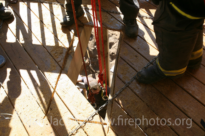 Climbing rope suspended from a tripod on the third floor supports people in the pit some 10 or 12 ft. below ground level