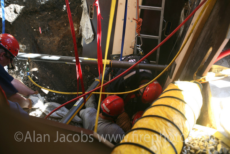 Shoring held firm by air pressure. Notice at the far left, just to the right of the partially cut off Special Operations firemen, a yellow tube attached to the Air Shore. This is attached on the other end to an air bottle and pressure gauges. The red tube is attached to the other Air Shore. Air is pushed under pressure through the  large, yellow accordion tube.